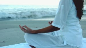 stock-footage-woman-relaxing-on-the-beach-practicing-yoga-in-slow-motion
